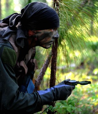 A soldier using navigation skills in his SERE training