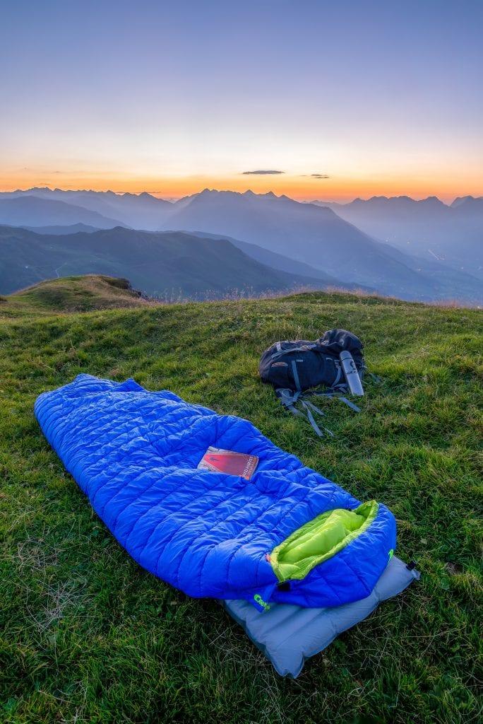 blue sleeping bag on mountain during daytime